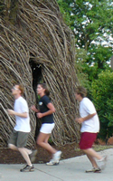 Photo of Dog Days group running passed bird's nest sculpture by Spooner Hall.