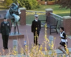 Photo of the KU Korean War Memorial with ROTC students standing vigil as the first runner comes by.